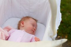 Newborn baby girl sleeping in a cradle outdoors. In a beautiful summer day royalty free stock images