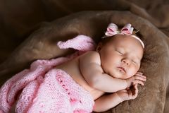 Newborn baby girl sleeping cute, covered with soft pink scarf, neatly folded under a pen with a small head with a pink bow, set royalty free stock photos