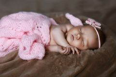 Newborn baby girl sleeping cute, covered with soft pink scarf, neatly folded under a pen with a small head with a pink bow, set royalty free stock photo