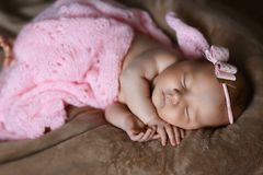 Newborn baby girl sleeping cute, covered with soft pink scarf, neatly folded under a pen with a small head with a pink bow, set royalty free stock image