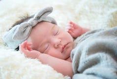Newborn baby girl is sleeping on fur blanket stock photos