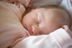 Newborn baby girl sleeping in her crib Stock Images