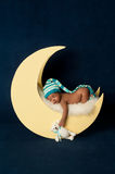 Newborn Baby Girl Sleeping on the Moon. Studio portrait of a four week old newborn baby girl wearing a stocking cap and leg warmers. She is sleeping on a moon Royalty Free Stock Images