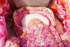 Newborn baby girl sleeping in a stroller Stock Image