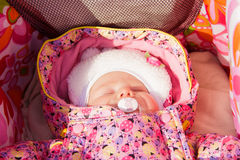 Newborn baby girl sleeping in a stroller Royalty Free Stock Photo