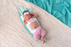 Newborn Baby Girl Sleeping on a Surfboard. Nine day old newborn baby girl sleeping on a tiny surfboard. She is wearing pink and white crocheted boardshorts Royalty Free Stock Photos