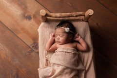 Newborn Baby Girl Sleeping in Tiny Bed. Overhead shot of a four week old newborn baby girl sleeping on a tiny, rustic wooden bed. Shot in the studio on a wood Stock Images
