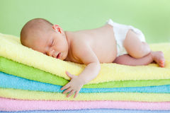 Newborn baby girl sleeping on towels Stock Image