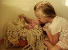 Newborn baby girl sleeping under cozy blanket in basket. Studio photo of cute beautiful newborn baby girl sleeping in basket. sister looking on baby with love Royalty Free Stock Photos