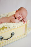 Newborn Baby Girl Sleeping in Yellow Drawer Stock Images