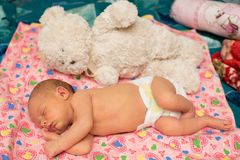 Newborn baby girl  sleeps with toy on bed. Newborn baby girl sleeps on bed. Use it for a child, parenting or love concept Royalty Free Stock Photography