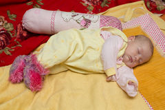 Newborn baby girl sleeps on bed. Stock Photo