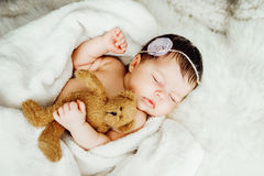 Newborn baby girl sleeps wrapped in white blanket. Stock Image