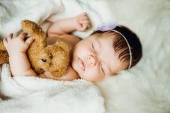 Newborn baby girl sleeps wrapped in white blanket. Royalty Free Stock Image