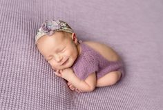 Little newborn baby girl in purple bodysuit smiling while sleeping stock images