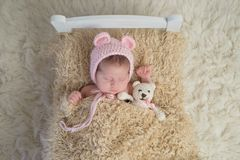 Newborn Baby Girl with Stuffed Bear. Portrait of a newborn baby girl. She is sleeping in a tiny bed with a stuffed bear and wearing a bonnet with bear ears stock photo