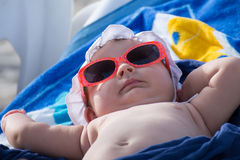 Newborn baby girl sunbathing. Newborn baby girl with red sunglasses sunbathing and relaxing Stock Photos