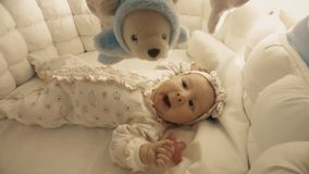 Newborn baby girl about to sleep in her cot Stock Photo