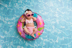 Newborn Baby Girl Wearing a Bikini and Sunglasses. Nine day old newborn baby girl sleeping on a tiny inflatable swim ring. She is wearing a crocheted pink and Stock Images