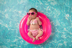 Newborn Baby Girl Wearing a Bikini and Sunglasses. Ten day old newborn baby girl lying on a tiny, inflatable swim ring. She is wearing a pink bikini and royalty free stock photo