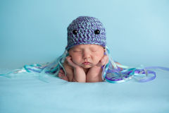 Newborn Baby Girl Wearing a Jellyfish Costume. Seven day old newborn baby girl wearing a crocheted jellyfish hat and sleeping on blue knit fabric Royalty Free Stock Photos