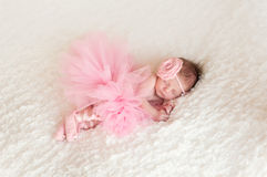 Newborn Baby Girl Wearing a Ballerina Tutu. Newborn baby girl wearing a pink crocheted headband, ballerina tutu, and ballet slippers. She is sleeping on white Royalty Free Stock Image