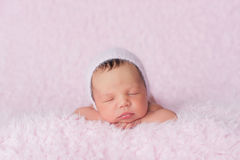 Newborn Baby Girl Wearing a Pink Knitted Bonnet Royalty Free Stock Images