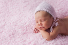 Newborn Baby Girl Wearing a Pink Knitted Bonnet Royalty Free Stock Photography