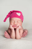 Newborn Baby Girl Wearing a Pink Top Knot Cap. A portrait of a beautiful eleven day old baby girl wearing an upcycled pink top knot cap with heart detail. She is Royalty Free Stock Images