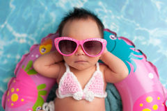 Newborn Baby Girl Wearing Sunglasses and a Bikini Top. Nine day old newborn baby girl wearing pink sunglasses and a pink and white bikini. She is sleeping on a stock image