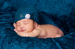 Newborn Baby Girl Wearing a Teal Flapper Style Hat. 8 day old newborn girl sleeping on a teal blanket and wearing a teal crocheted flapper-style hat with Royalty Free Stock Images