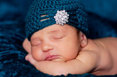 Newborn Baby Girl Wearing a Teal Flapper Style Hat. 8 day old newborn girl sleeping on a teal blanket and wearing a teal crocheted flapper-style hat with Stock Photo