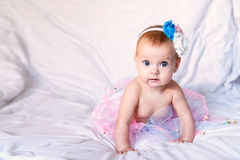 Newborn baby girl wearing a white crocheted crown, ballerina tutu, and ballet slippers. She is sleeping on pink rose. Newborn baby girl wearing a white crocheted Royalty Free Stock Photography