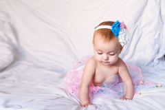 Newborn baby girl wearing a white crocheted crown, ballerina tutu, and ballet slippers. She is sleeping on pink rose. Newborn baby girl wearing a white crocheted Royalty Free Stock Photos