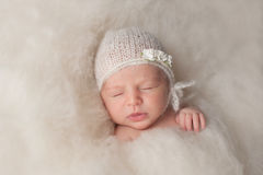 Newborn Baby Girl Wearing a White Knitted Bonnet Stock Photo