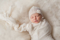 Newborn Baby Girl Wearing a White Knitted Bonnet Stock Photos