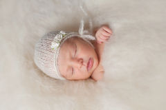 Newborn Baby Girl Wearing a White Knitted Bonnet Stock Images