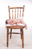 Newborn baby girl. With white blanket posed and sleeping on a wooden chair Royalty Free Stock Image