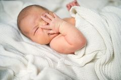 Newborn baby with a hand on her face lying on bed, covered by a white blanket. royalty free stock photos