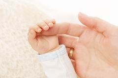 Newborn baby hand holding parent finger. Newborn baby hand holding parent mother finger royalty free stock image