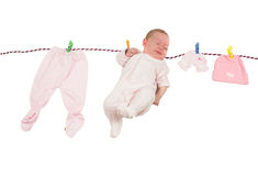 Newborn baby hanging on clothespins with linen isolated Royalty Free Stock Photography