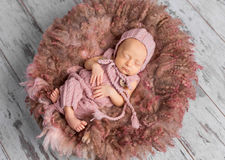 Newborn baby in hat and jumpsuit sleeping in round bed Stock Photography