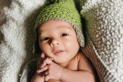 A newborn baby in a hat lies in a crib. Royalty Free Stock Image