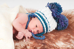 Newborn baby in hat with pom-pom Royalty Free Stock Photo