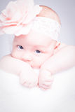 Newborn baby with headband on the head lying on blanket. Stock Photo