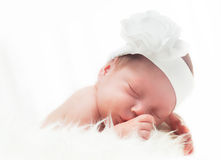 Newborn baby with headband sleeping on white fur Royalty Free Stock Image