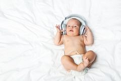 Newborn baby with headphones. Little newborn baby with headphones on white bed royalty free stock images
