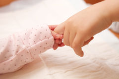 . Newborn baby holding finger of older child. Royalty Free Stock Photos