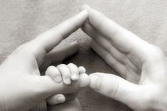 Newborn baby holding his hand on the fingers of parents