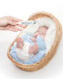 Newborn Baby In Basket With Temperature Meter Stock Image
